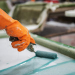 Worker's hand in orange glove rolling solution on fiberglass sheet at a factory