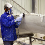 Male with protective wear grinding a fibre glass unit. Note: lots of dust in the air due to the grinding